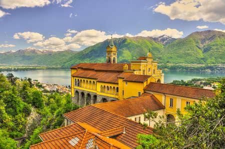 The Madonna del Sasso monastery in front of the Lake Maggiore and mountains in Locarno, Ticino, Switzerland