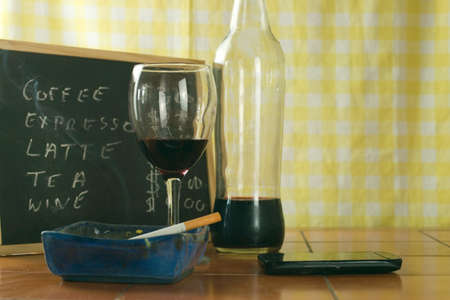 A glass of red wine, cigarette and a mobile phone on the table 免版税图像