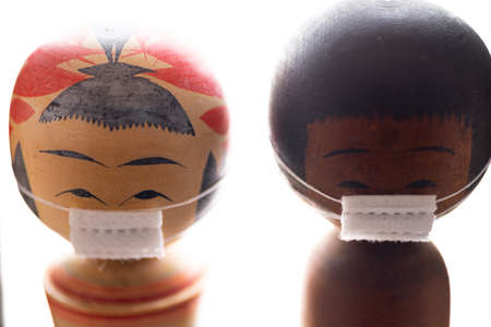 A shallow focus shot of wooden Asian dolls wearing medical masks during Covid-19 - the new normal
