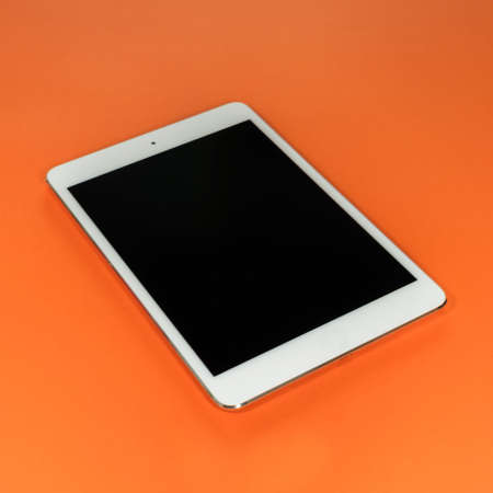 A single white tablet on an orange background Banque d'images