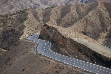 A curvy road around the cliff with mountains in the background