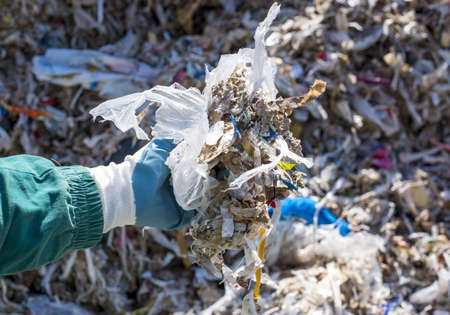 A closeup shot of a person holding shredded municipal waste used as an alternative fuel