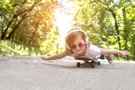 A happy kid with headphones and sunglasses lying on a skateboard in a park under the sunlight