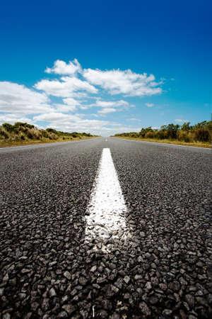 A vertical shot of an asphalt road under the blue sky