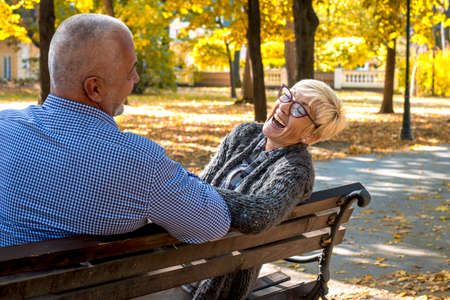 An elderly couple laughing and having fun on a park bench