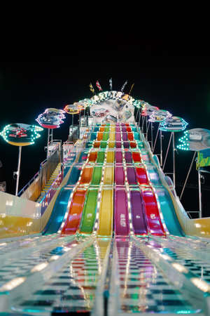 A low shot of colorful water slides at the park during a carnival at night