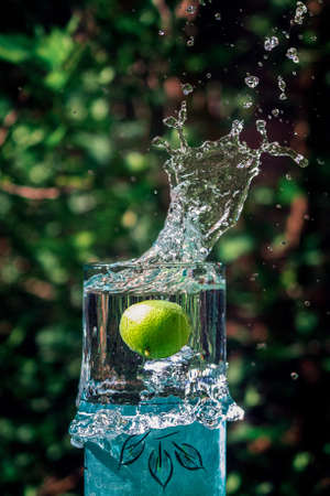 A vertical shot of a green fruit dropped in a pitcher full of water that created a splash
