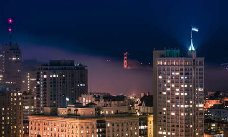 A beautiful shot of the downtown San Fransisco building with the golden gate bridge visible in the distance at night time