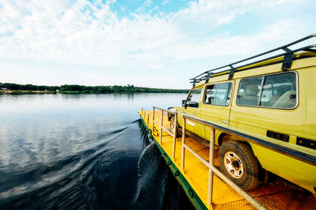 A wide shot of a yellow van on a yellow dock by the sea under a clear sky with clouds 写真素材