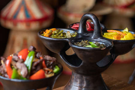 A selective focus shot of delicious Ethiopian food with fresh vegetables on a wooden table