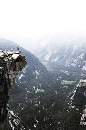 A person standing at the edge of a rocky mountain. Stock Photo
