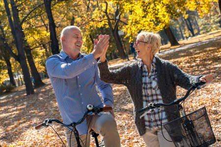 An elderly couple standing with their bikes, smiling and high-fiving in a park