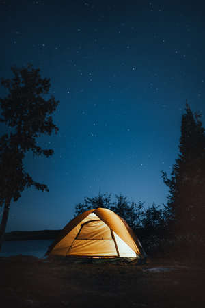 A vertical shot of a camping tent near trees during nighttime Stock Photo
