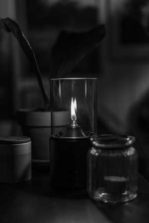 A depressing shot of decorative lit candle in black and white