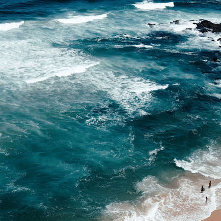An aerial overhead shot of the beautiful coast of the sea with amazing water textures and people on the beach
