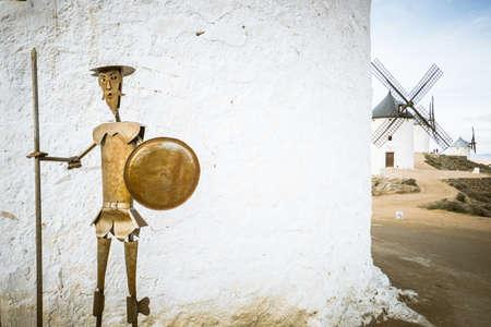 A beautiful shot of the bronze Don Quijote sculpture near the white windmill wall in Consuegra, Spain Foto de archivo