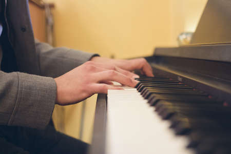 A closeup shot of a musician playing on piano with hands in focus