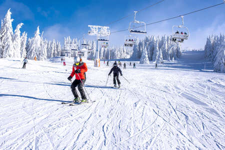 The skiers skiing in a mountain resort with a ski lift in the background
