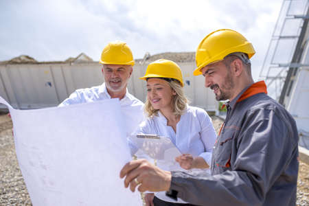 A group of construction workers looking at the plans and documents under the sunlight Stockfoto