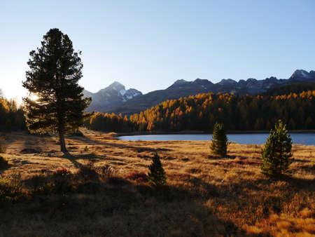 A breathtaking shot of a lake near a dry grassland on a mountain landscape background