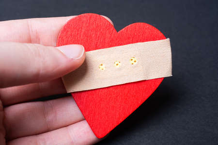 A closeup of a person's hand holding a red wooden heart with an adhesive bandage