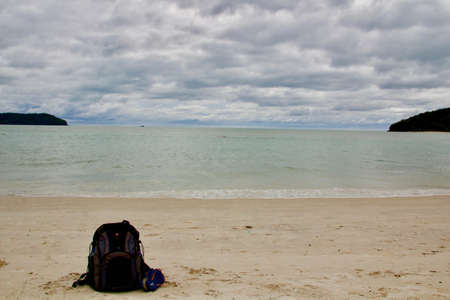 A horizontal shot of a beach with a traveling bag where the cloudy sky is visible in the background Stock fotó