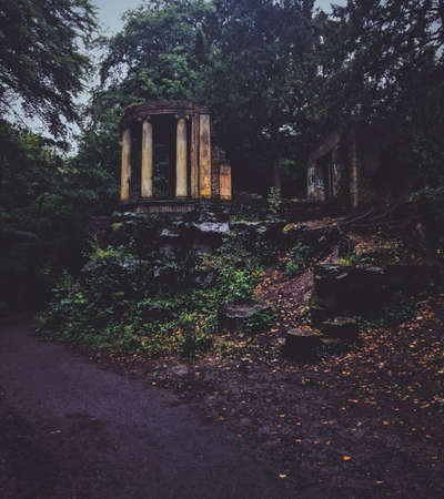 A vertical shot of an abandoned building with pillars on a hill surrounded by trees and plants