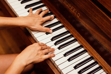 A closeup shot of a person's hands playing brown piano Stockfoto