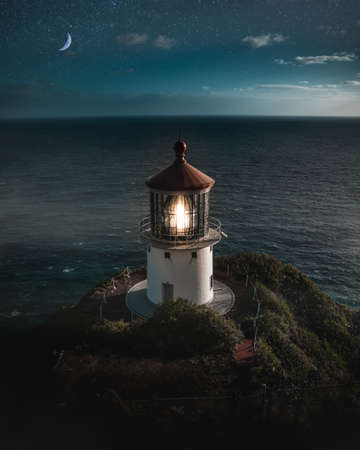 A beautiful aerial shot of a lit lighthouse on a green hill with the half-moon in the beautiful night sky and the ocean in the background