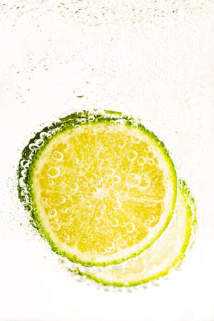 A vertical shot of sliced lime submerged in the water with a white background