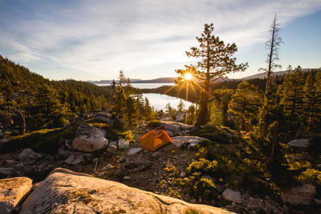 A beautiful shot of an orange tent on rocky mountain surrounded by trees during sunset