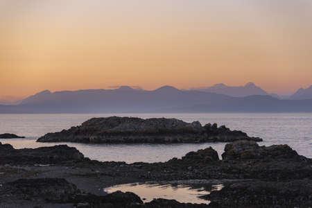 A beautiful shot of rocky cliffs near sea under a pink sky