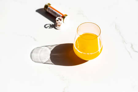 A closeup shot of immune-boosting multivitamin effervescent tablet and a glass of juice