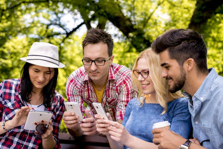 A group of Caucasian friends playing with smartphones in the park