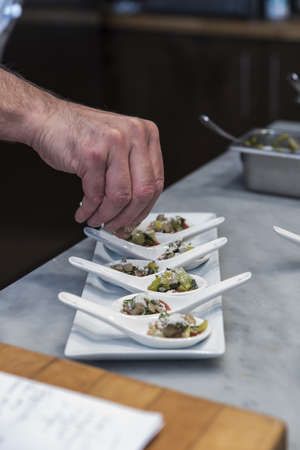 A closeup of a chef's hand fixing appetizers in white spoons on a white tray