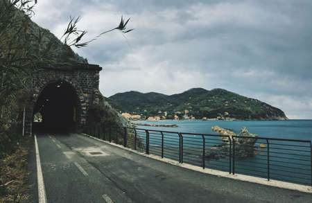 A road towards a tunnel in the mountain near a sea with mountains in the background