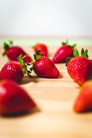 The sweet red strawberries on a wooden table