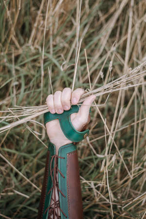 A closeup shot of a person wearing hand armor holding dried grass in his hand