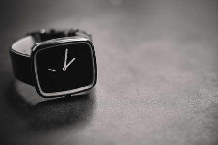 A dark analog clock on a metallic surface Stok Fotoğraf