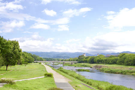 A landscape shot of a river in Kyoto during summer with a bridge visible in the distance