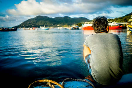 An adult male squatting on a pier next to docked ships and beautiful calm water