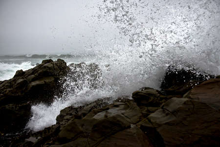 A beautiful splash of ocean waves on rocks during a rainy day