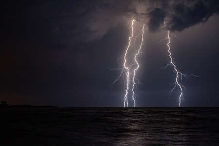 A beautiful scenery of lightning over the stormy sea at night Foto de archivo