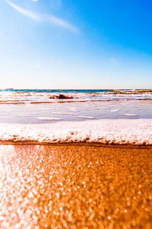 A sunny scenery of a beautiful sandy beach on a blue seascape background