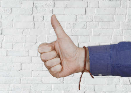 A closeup of a person doing the thumbs-up gesture with a white wall on the background