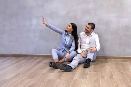 An excited young couple sitting on the floor of empty new apartment and planning arrangement