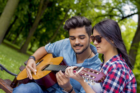 A young romantic couple playing the guitar sitting on a wooden bench in a park