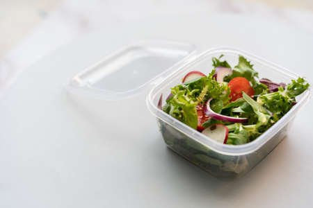 A closeup shot of fresh salad in a plastic box on a white surface