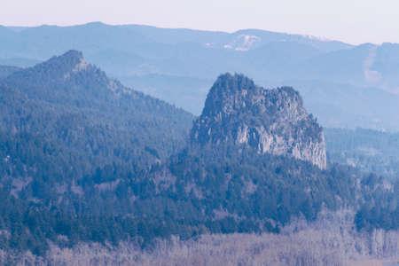 A single rocky mountain in a forest with hills in the background Фото со стока