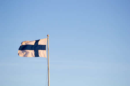 A closeup of the flag of Finland waving on a pole against a blue sky Zdjęcie Seryjne